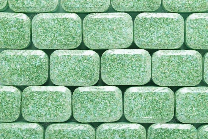 Green dishwasher detergent tabs background or texture.