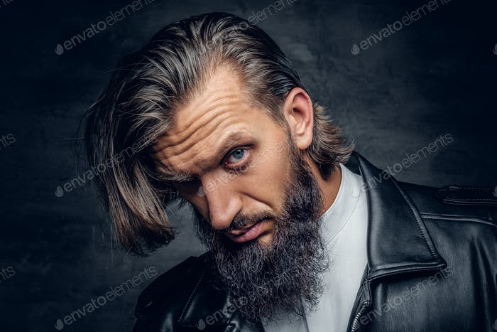 Bearded male with long hair on grey background.