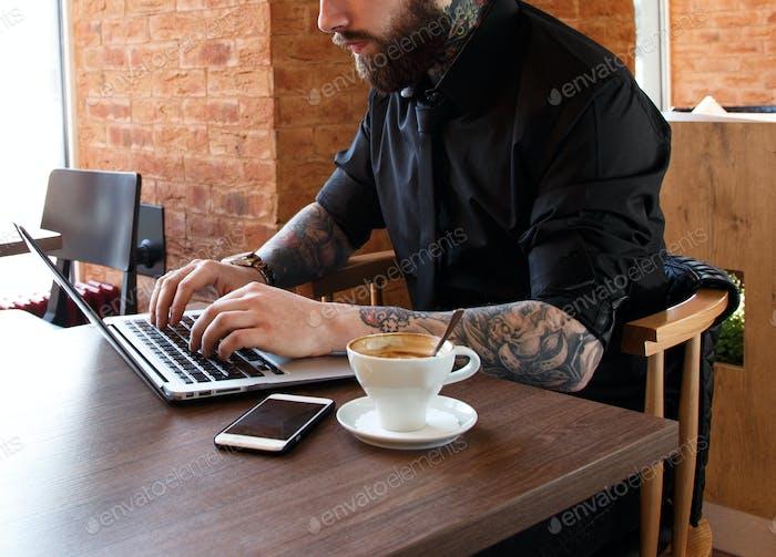 Hombre serio que Trabajo en la Ordenador portátil