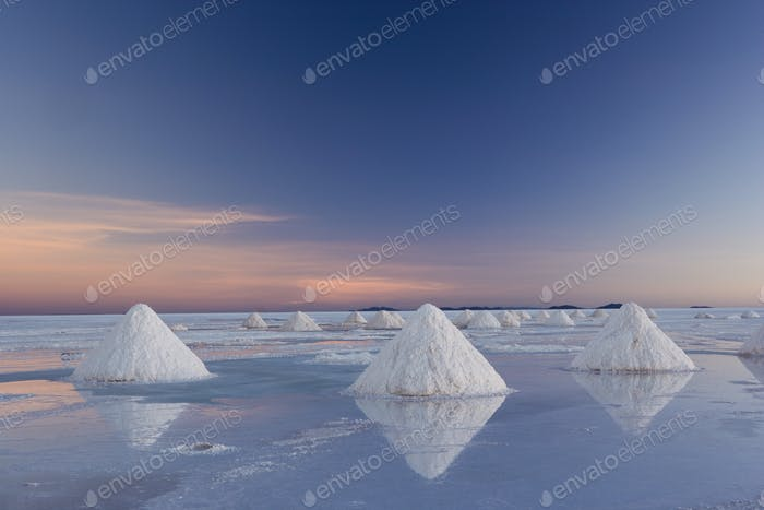 The salt pans of Salar de Uyuni, with shallow water and mineral deposits. White salt granules raked