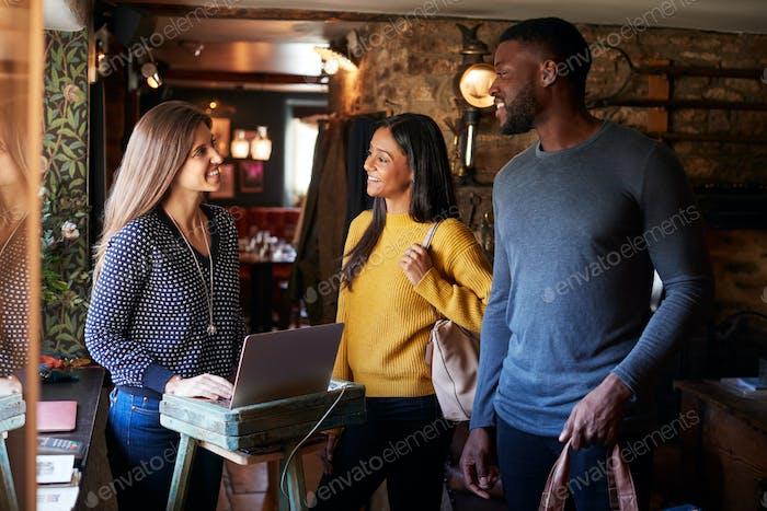 Приемник приветствуя гость пару, как они проверить в отель