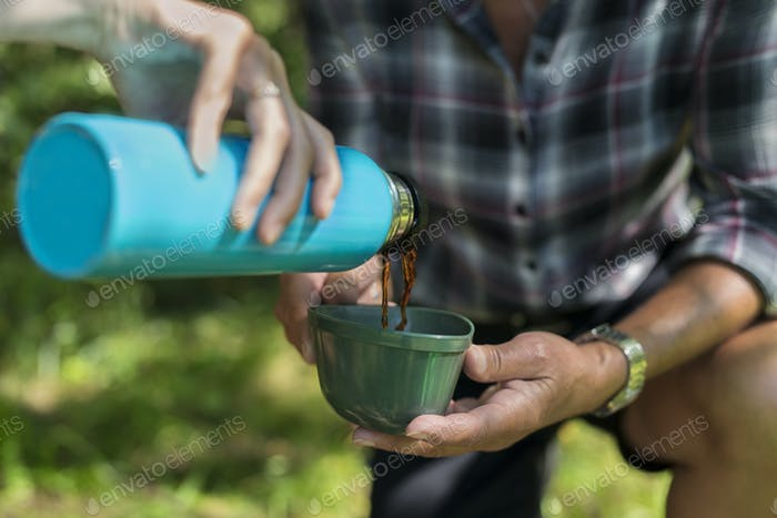 Young woman pouring drink from insulated drink container