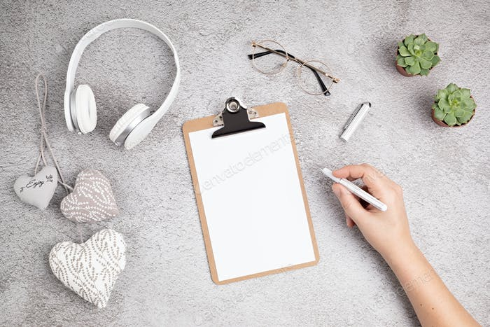 Blank clipboard, glasses, white pen and earphones on grey concrete background