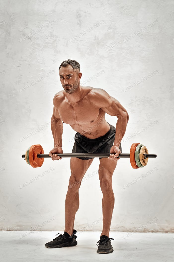 Shirtless adult athlete doing an exercise with a barbell in a bright studio