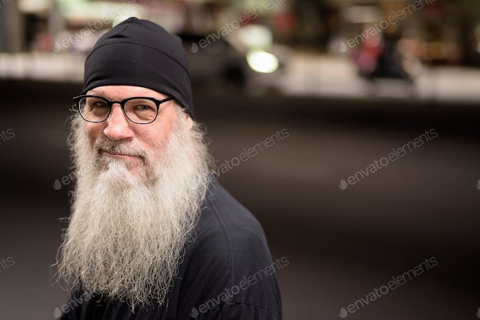 Face of happy mature bearded hipster man with eyeglasses in the city streets