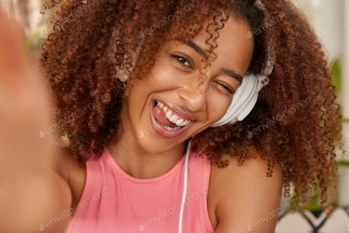 Positive curly Afro American girl blinks eyes, shows tongue, being in good mood, hears melody in hea