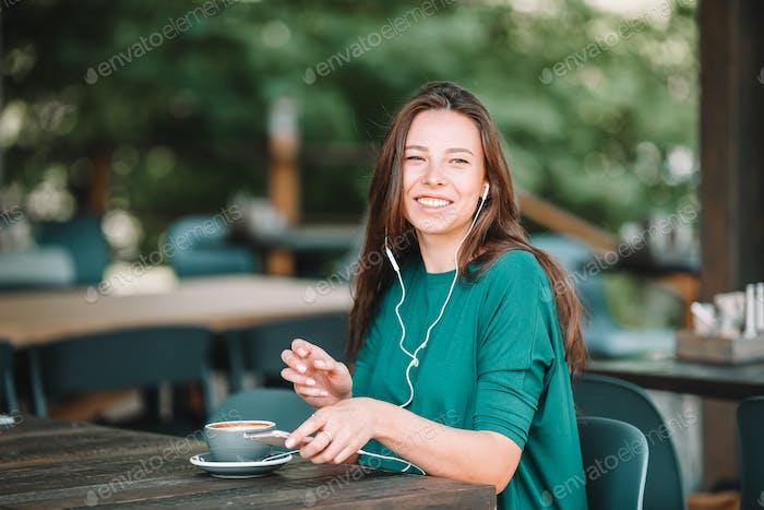 Schöne Frau mit Frühstück im Café im Freien. Glückliche junge Stadtfrau trinken Kaffee