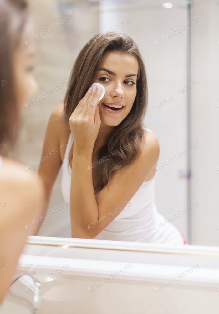 Woman removing makeup from her face