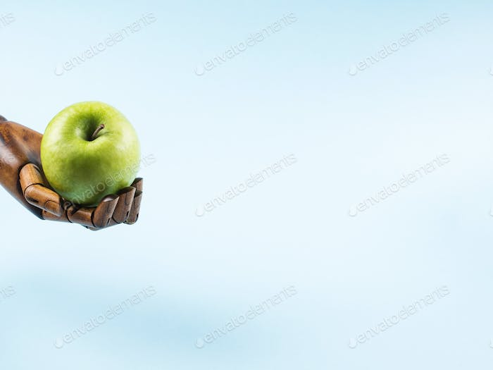Fresh green apple in palm of wooden hand on blue