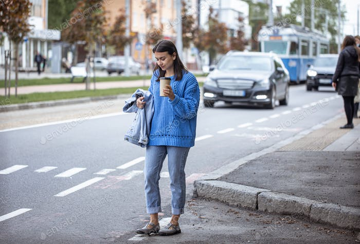 Street portrait of smiling young woman with coffee.