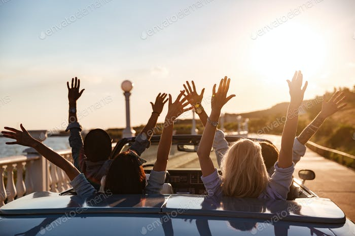 Back view of happy friends driving cabriolet with raised hands