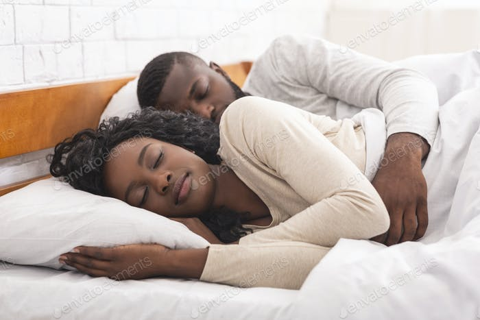 Afro couple sleeping together in comfortable bed at home
