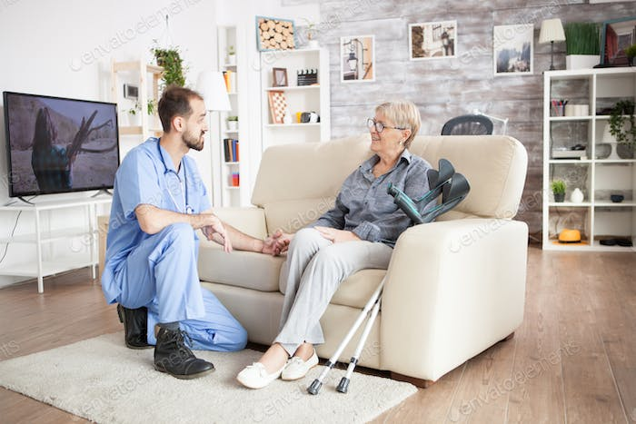 Male care taker in a nursing home holding arm of old woman