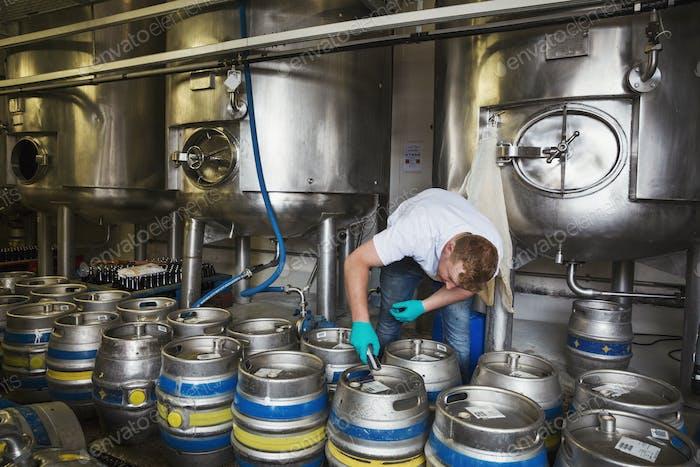 Man working in a brewery, closing metal beer kegs.