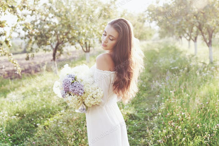 Beautiful young woman wearing elegant white dress and enjoying beautiful sunny afternoon in a summer