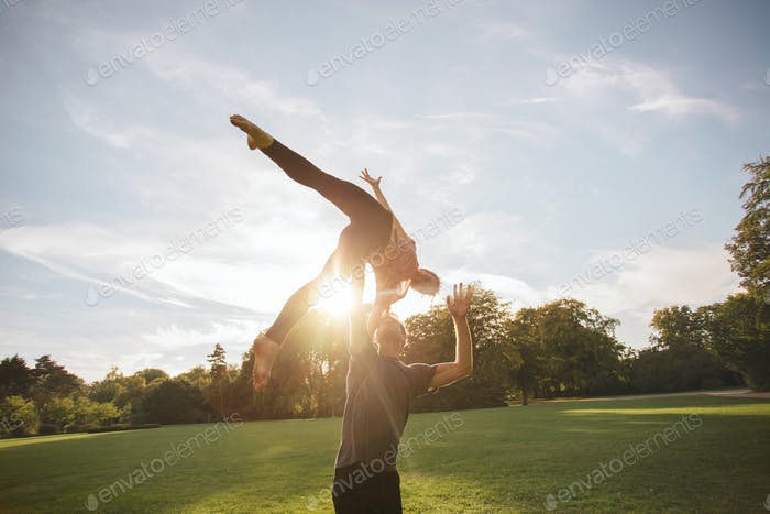 Fit couple doing acroyoga in park