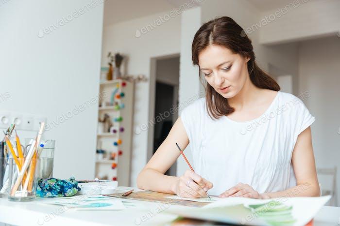 Beautiful inspired woman painter painting in art studio