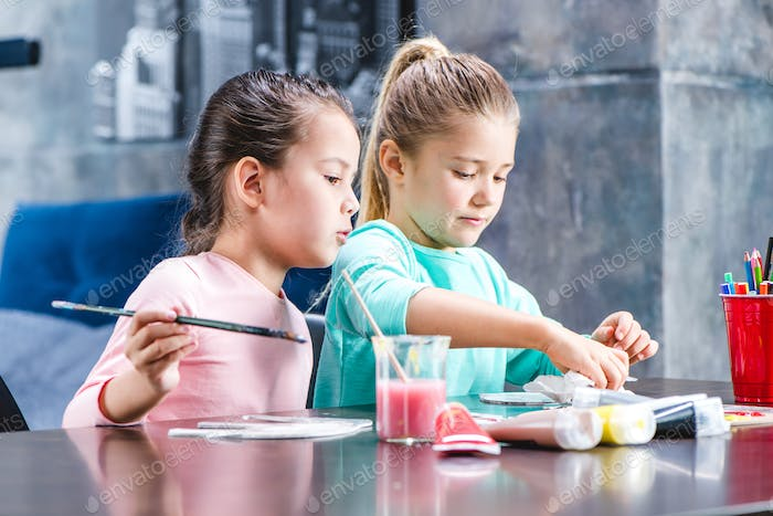 Children sitting at table and painting animals on paper