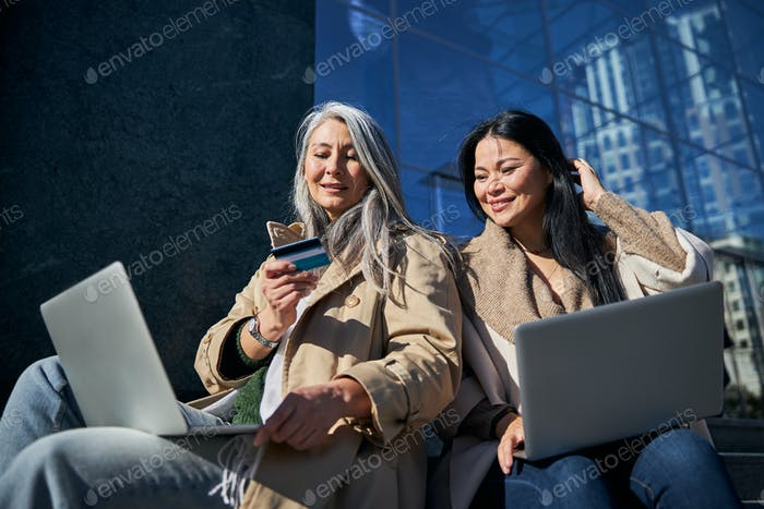 Schöne Freundinnen benutzen Laptops für Online-Shopping
