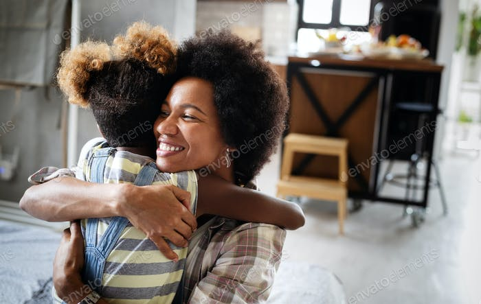 Portrait of a joyful mother and her daughter smiling and hugging
