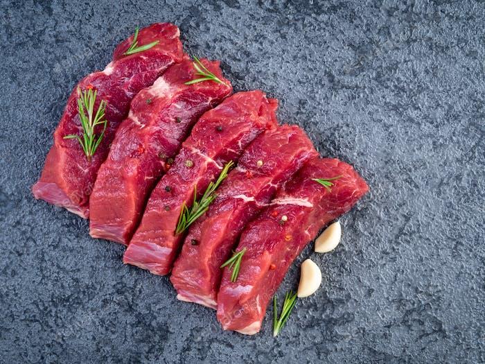 Rohes Fleisch, Rindersteak mit Gewürz auf einem schwarzen Steintisch, Draufsicht