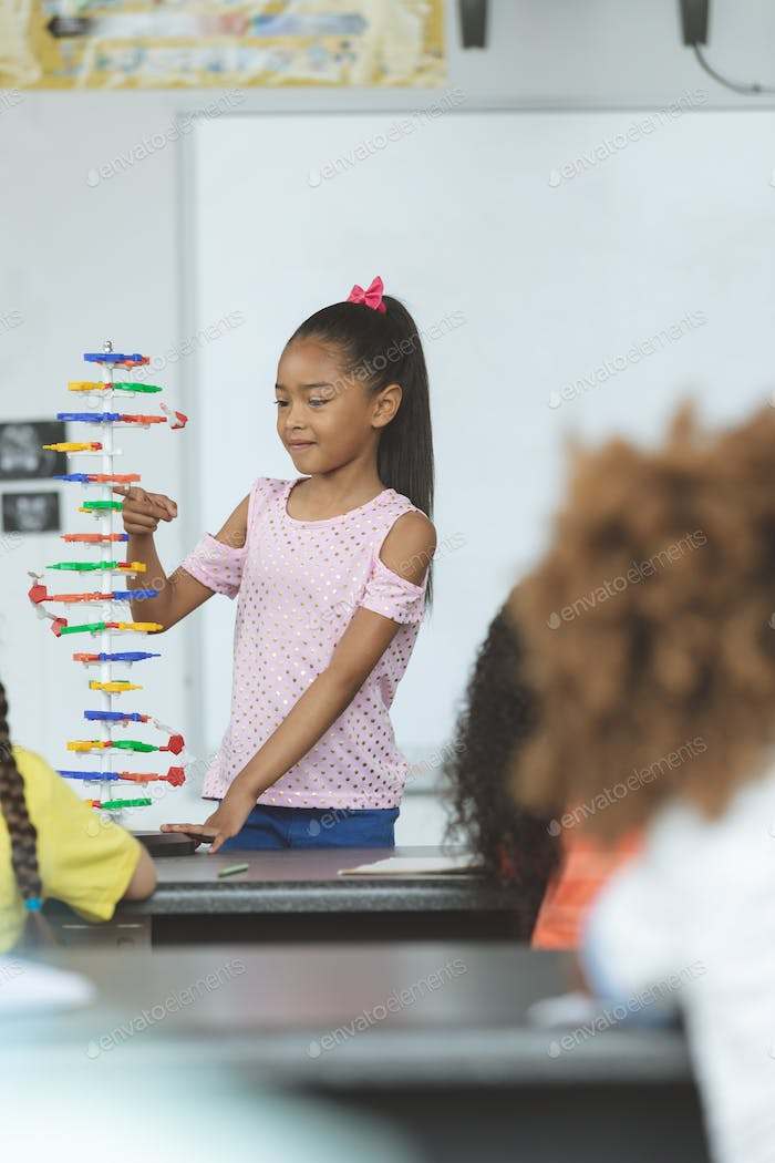Front view of a mixed-race ethnicity schoolgirl analyzing DNA structure model in classroom at school
