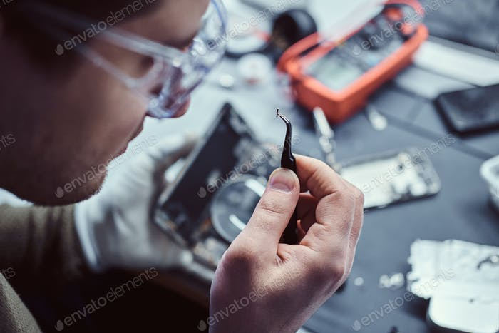 Electronic technician repair damaged smartphone in the workshop