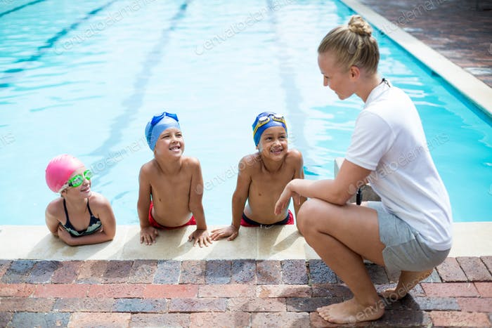 Female trainer teaching students at pool side