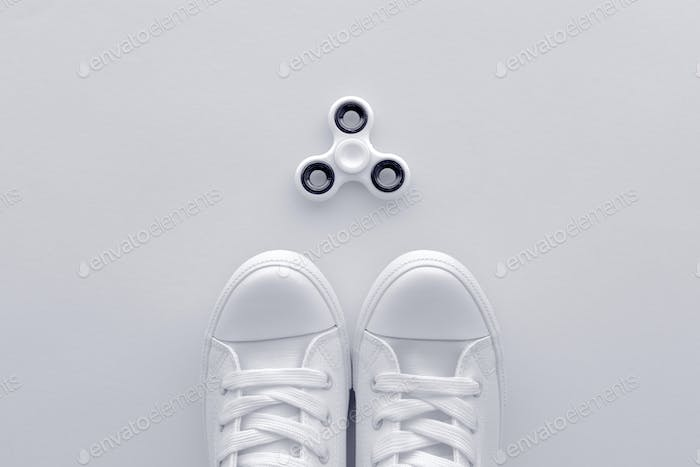 Sneakers and fidget spinner flay lay top view