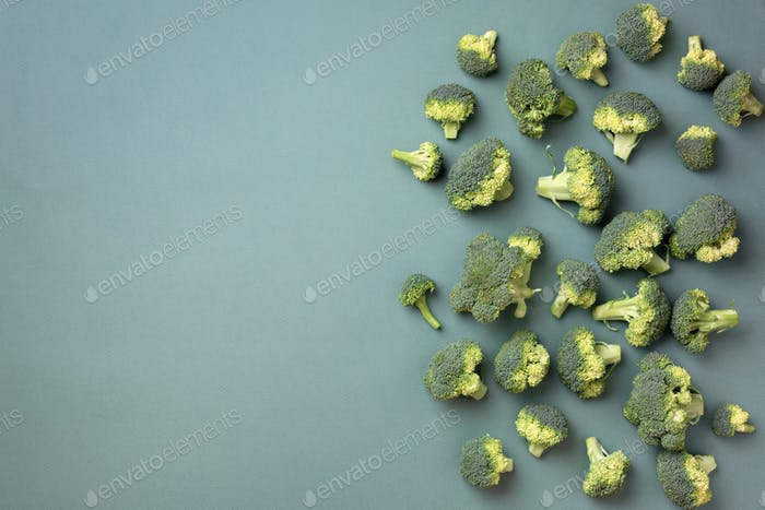 Creative layout of fresh broccoli on green paper background. Top view. Food pattern in minimal style