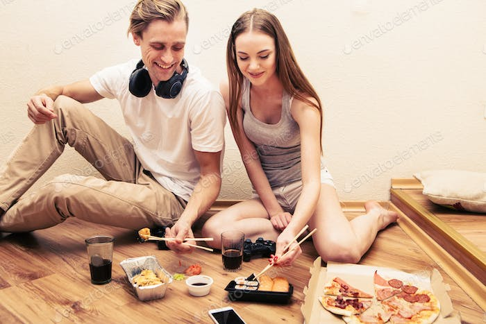 Young couple eat sushi at home together. Indoor filming.