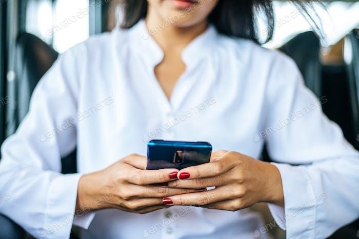 woman wearing white clothes and sitting play smartphone