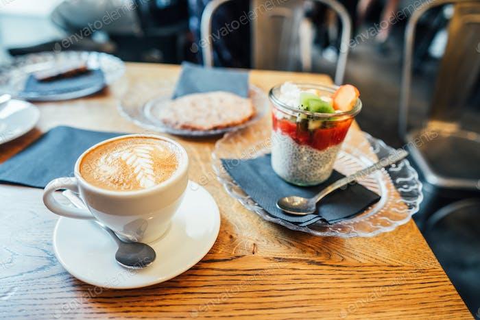Cappuccino mit Löffel in Tasse und Dessert