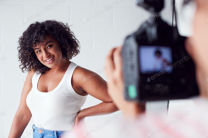 Model Posing For Female Photographer In Studio Portrait Session