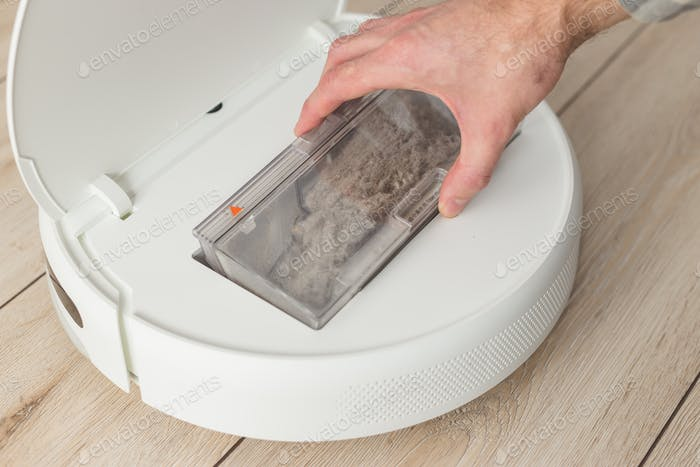 The hand pulls out a container of garbage from the robot vacuum cleaner