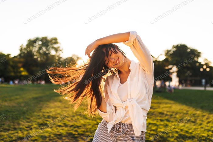 Beautiful smiling asian girl in white shirt happily dancing whil