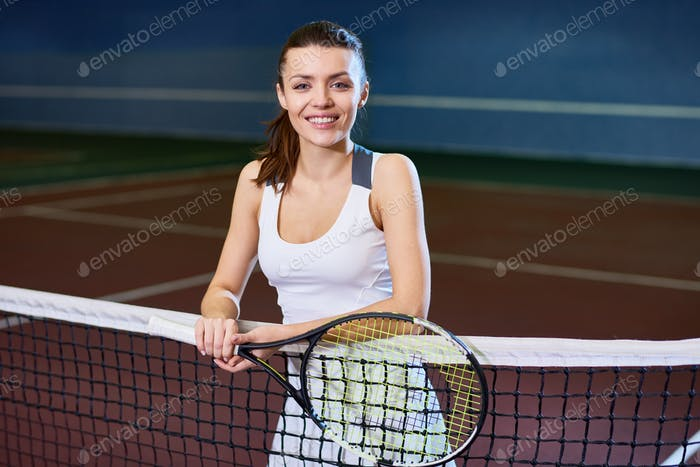 Smiling Young Woman Posing in Tennis Court