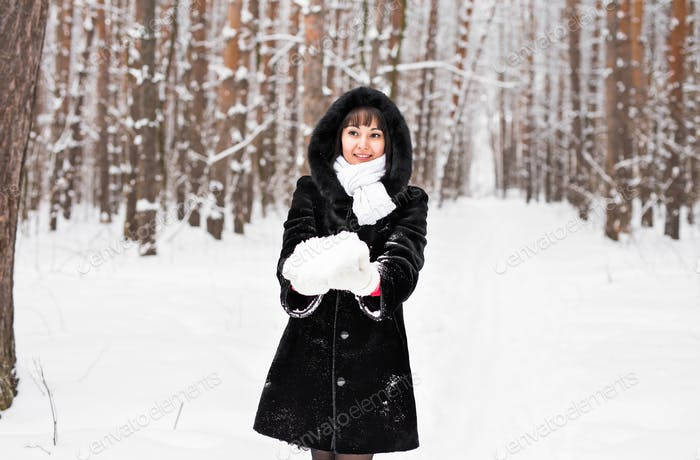 young woman in fur coat outdoors in snow garden
