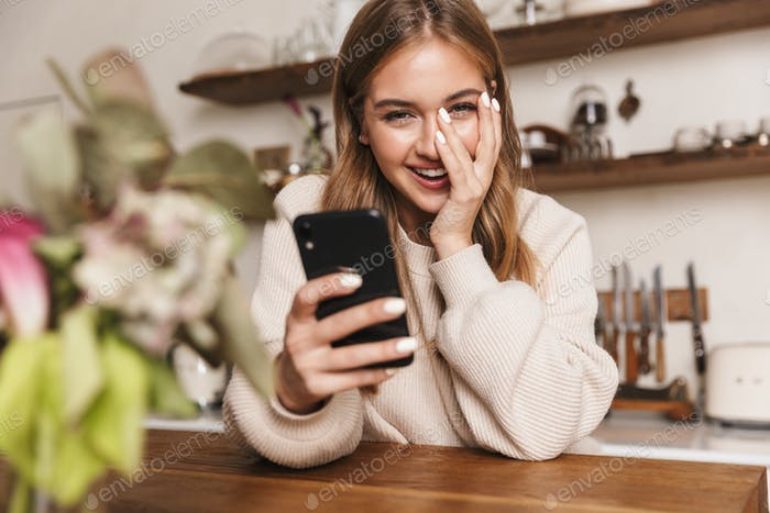 Image of happy caucasian woman using smartphone and laughing