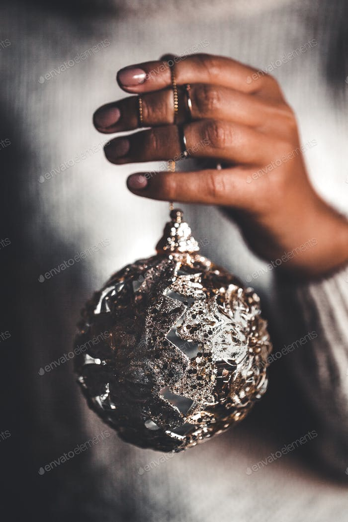 Woman in warm sweater holding toy glass decorative ball in hands, copy space. Christmas, new year