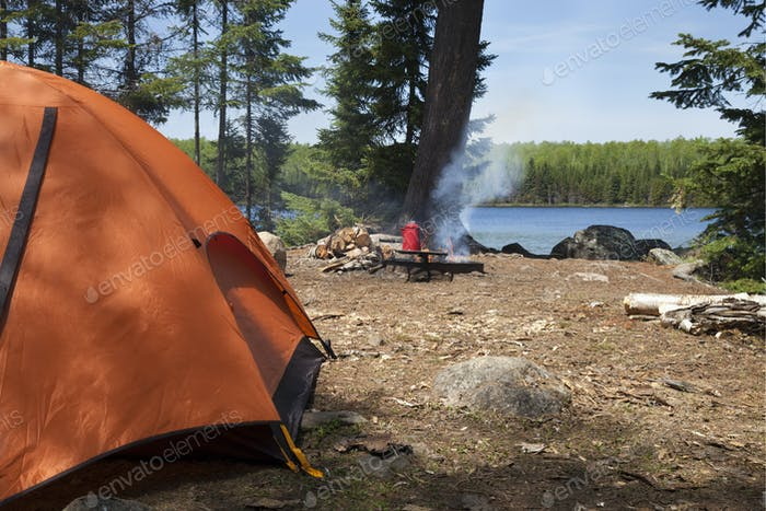 Campsite in northern Minnesota with orange tent and campfire