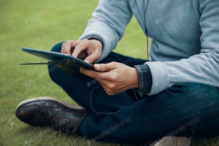 Crop man browsing tablet on grass