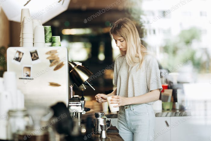 A young pretty thin blonde with long hair,dressed in casual outfit,is cooking coffee in a modern