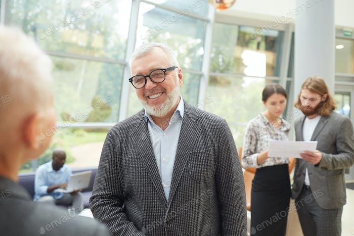 Smiling Senior Businessman Talking to Colleague