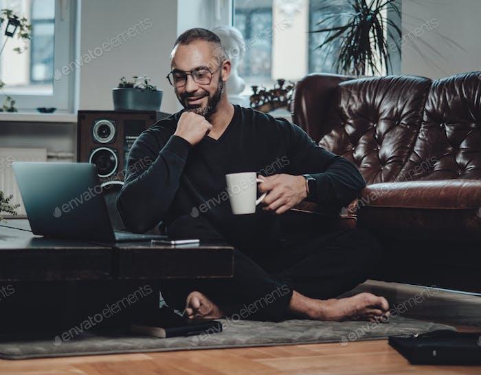 Chico alegre viendo algo en el ordenador portátil y relajarse en el apartamento