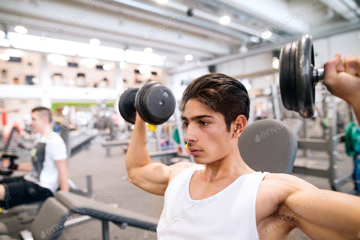 Hispanic man in gym on bench, working out with weights