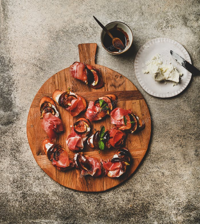 Crostini with prosciutto, cheese, figs over concrete table, top view