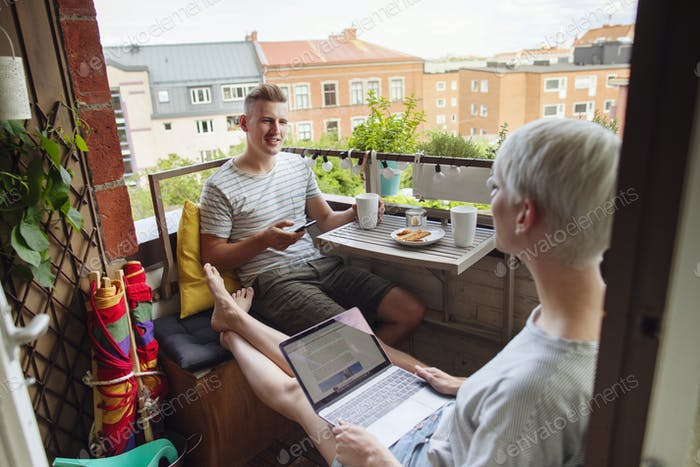 Couple using mobile devices on balcony