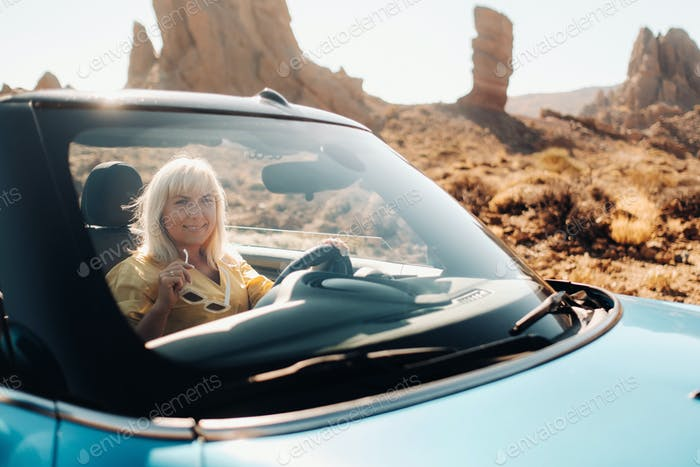 Girl in yellow dress enjoying a road trip in a convertible through a deserted valley with mountains