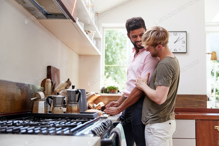 Male Gay Couple At Home In Kitchen Making Breakfast Together